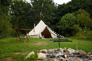 The campfire pit with cooking grill in the foregrojund with the glamping bell tent at the rear set back into the woodland