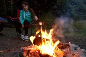 Relaxed teenager on a camping chair toasting marshmallows on a stick over a roaring camp fire