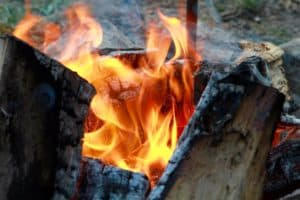 A roaring log campfire with yellow and orange flames