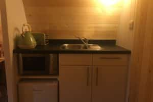 Camping kitchen in our ensuite pod showing the green toaster and kettle, fridge and microwave