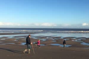 Children walking on deserted Chapel Six Marshes beach wrapped up in winter coats