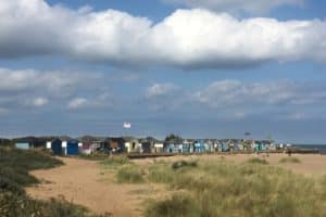 A sunny scene with blue skies looking over a row of beach huts at Chapel St Leonards
