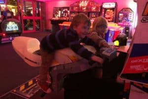 Young child laid on the arcade motorbike simulator at Skegness Arcade