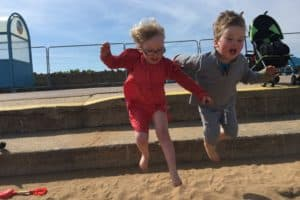 Twins jumping from the steps on Skegness Promenade into the golden sand